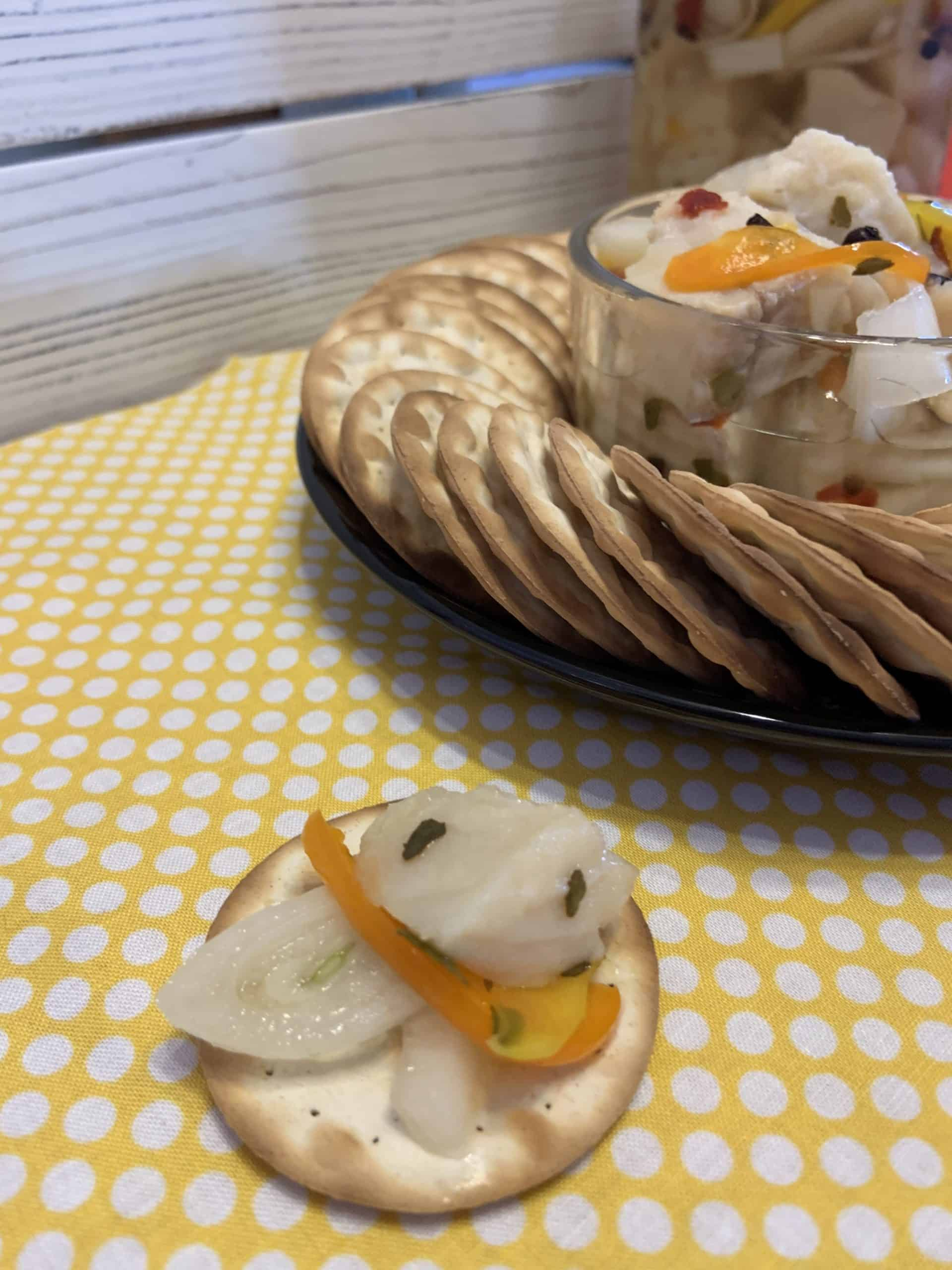 Pickled Fish on a cracker with a fish and crackers tray
