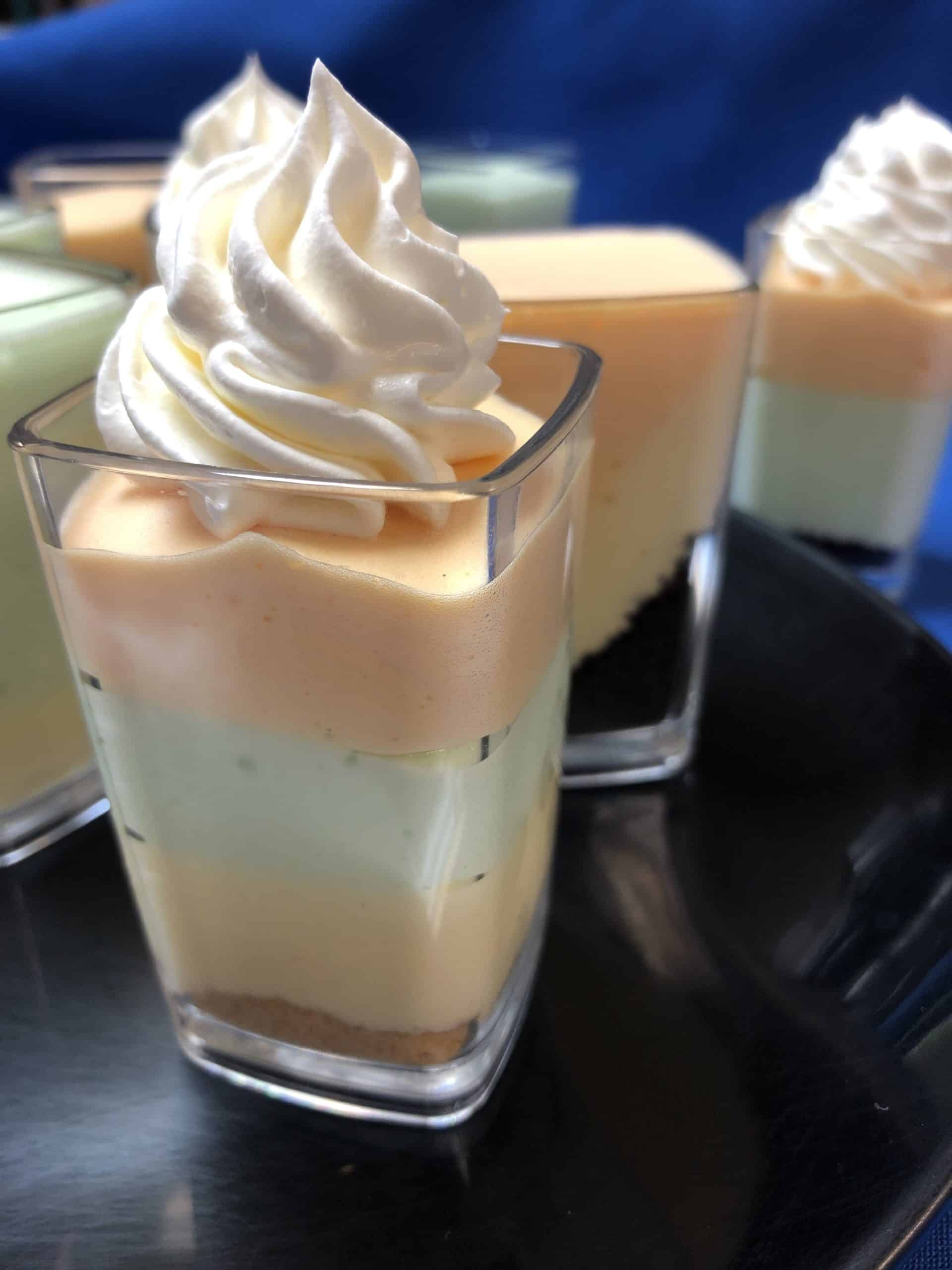 Layered Citrus No Bake Cheesecake in square clear serving cups.