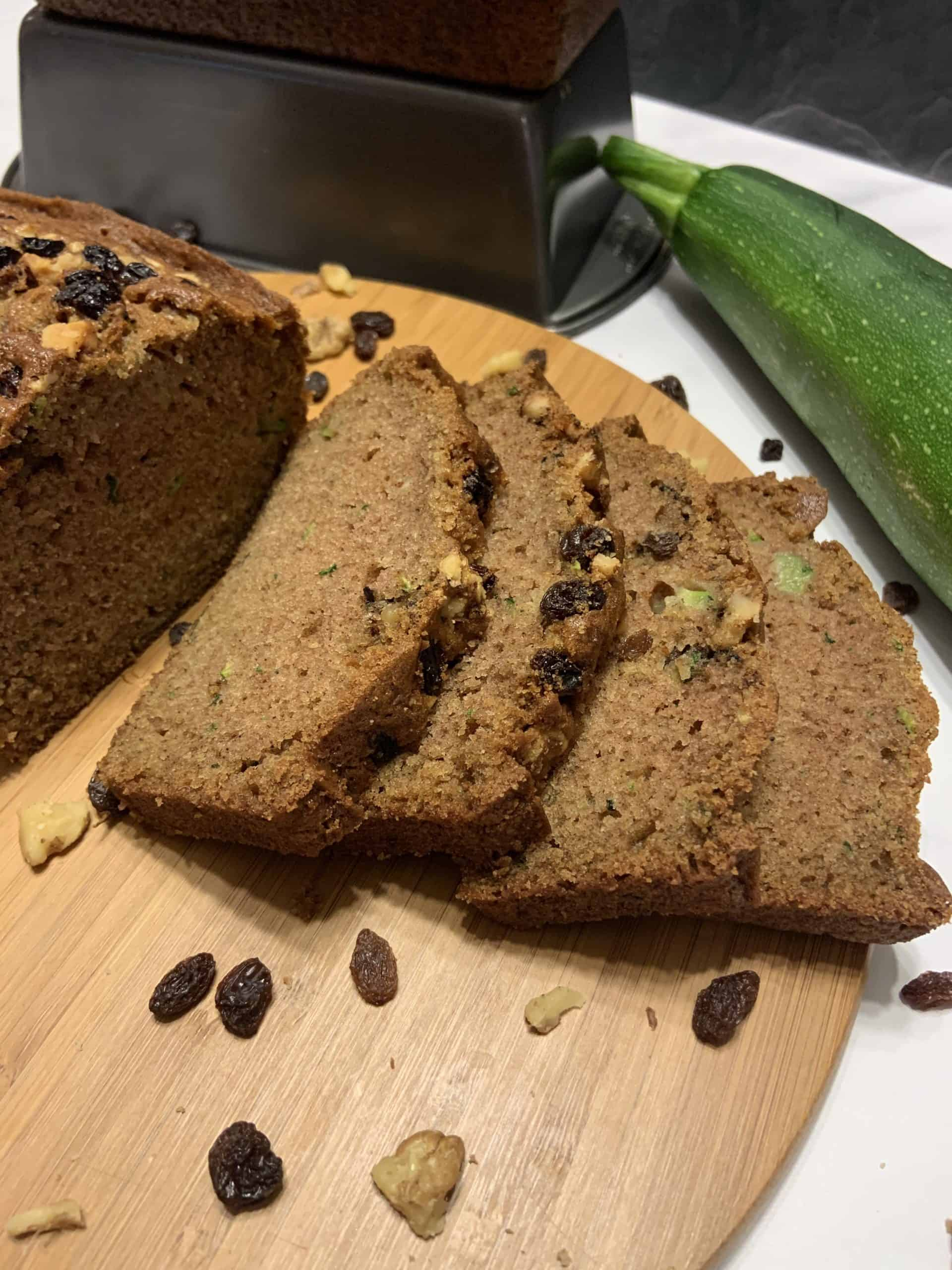 Zucchini Bread sliced on a wooden cutting board