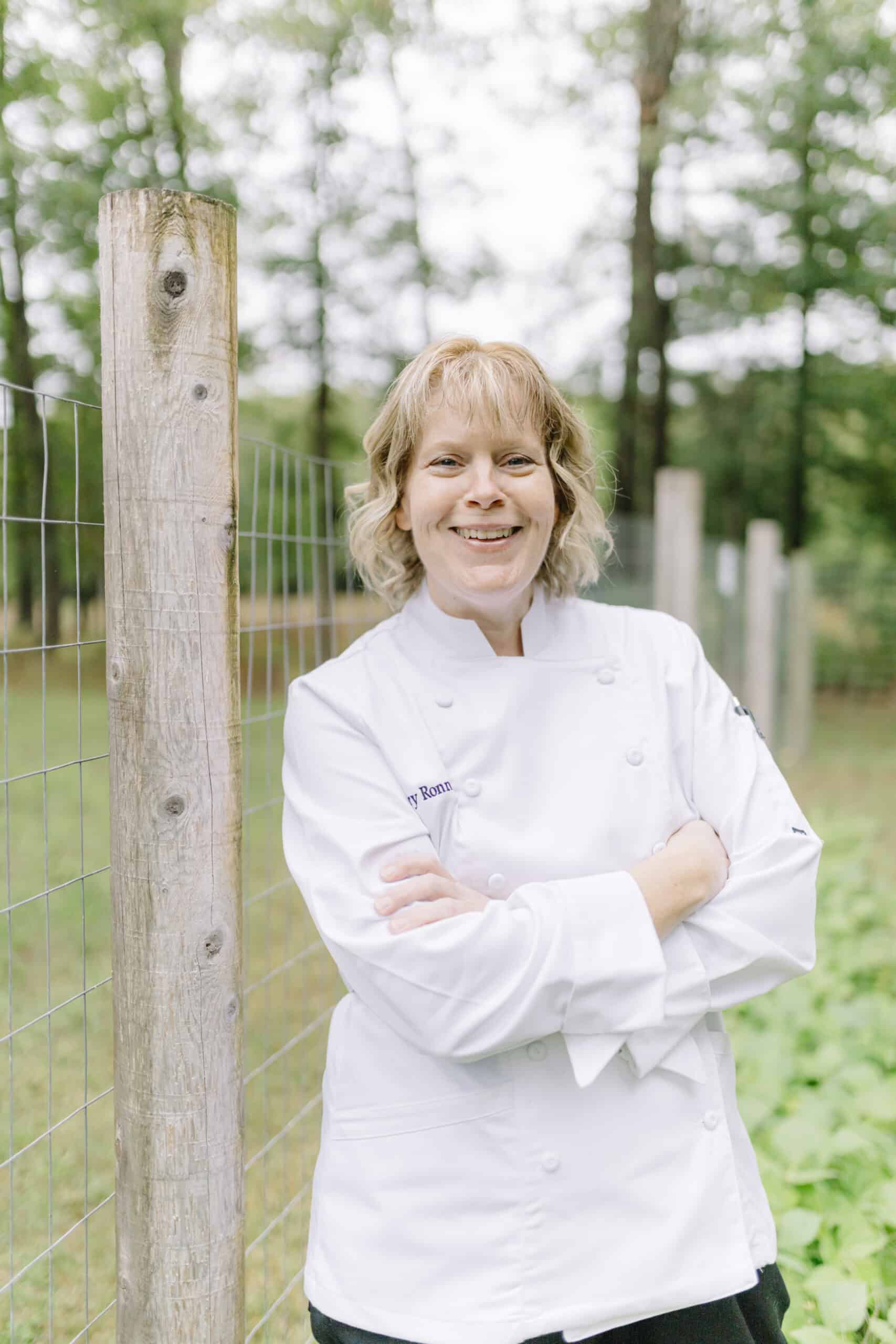 Sherry Ronning in a chef coat standing up against a garden fence.