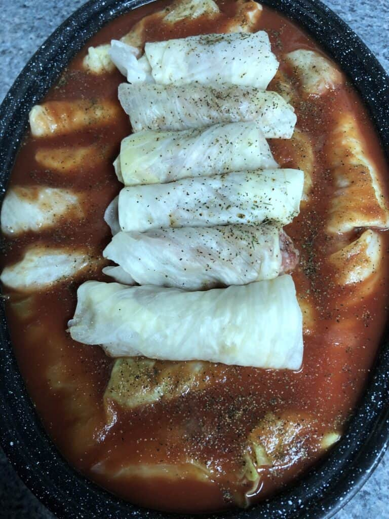Several cabbage rolls lined up in a roasting pan.