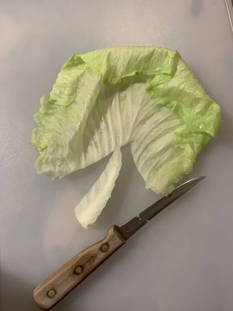 Cutting the vein off of the cabbage leaves.