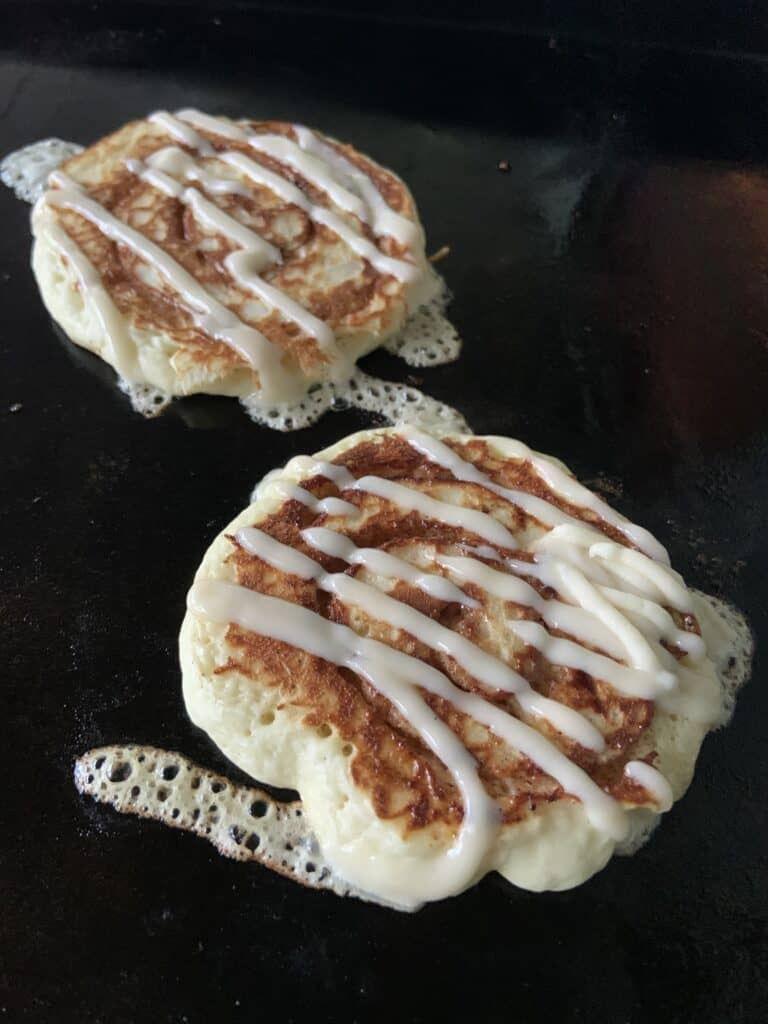 Cinnamon Swirl Pancakes on Griddle with Zig-Zag Icing