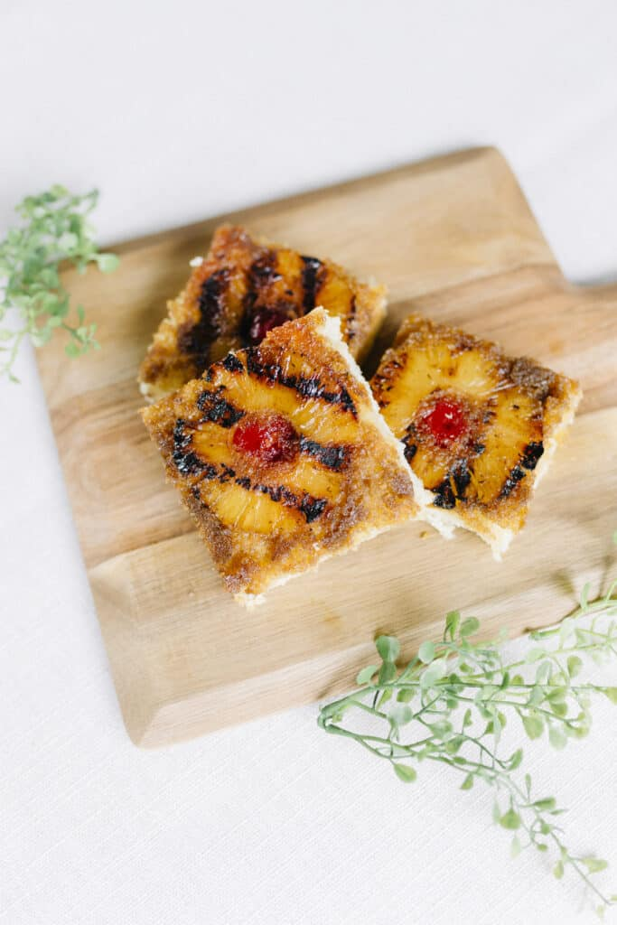 Brown butter grilled pineapple upside down cake pieces on a wooden board.