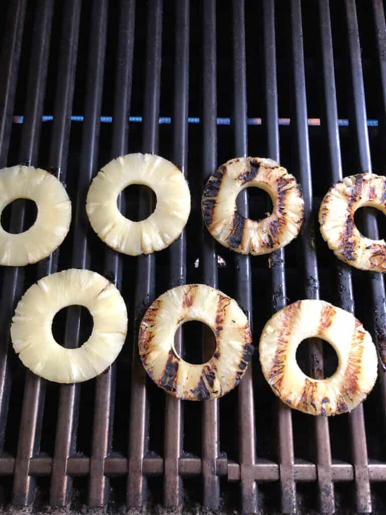 Grilled pineapple rings on the grill.