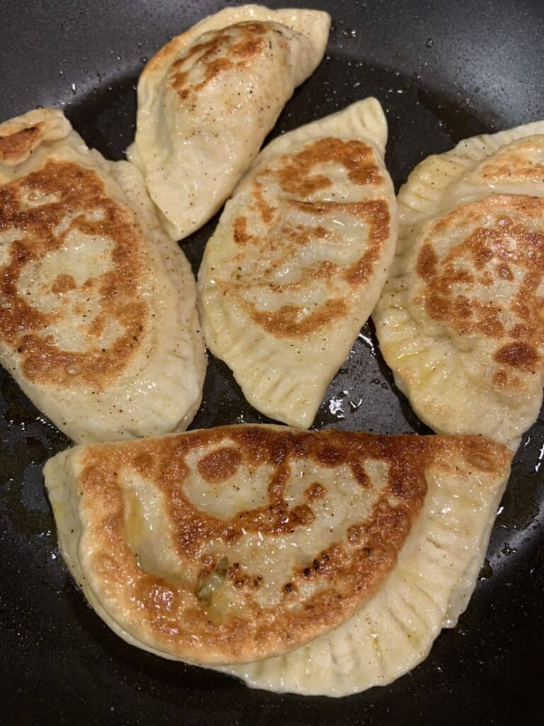 Cabbage Pierogies in a fry pan.