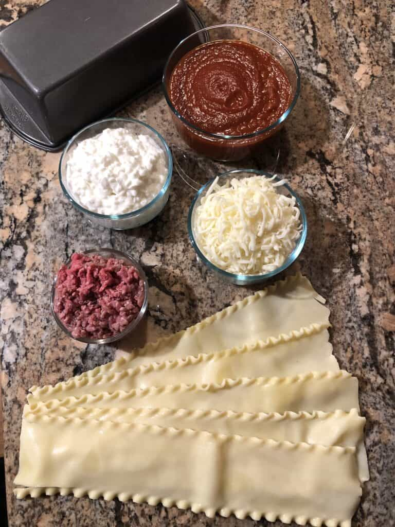 Lasagna ingredients - noodles, hamburger, sauce, cottage cheese, and mozzarella