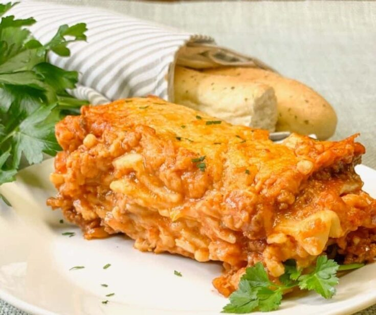 A slice of lasagna with bread sticks.