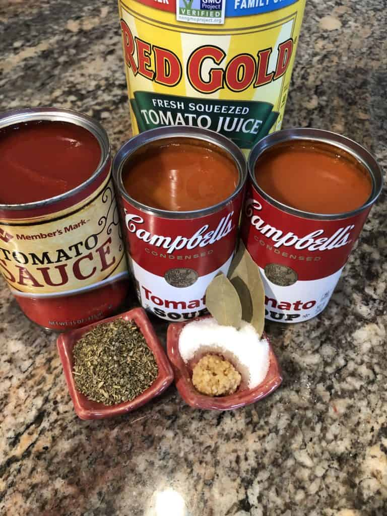 Spaghetti Sauce ingredients - tomato juice, sauce, and soup, diced onion, hamburger, Italian seasoning, bay leaves, garlic, and sugar.