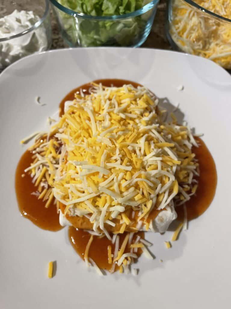 Shredded Cheese onto of enchilada sauce.