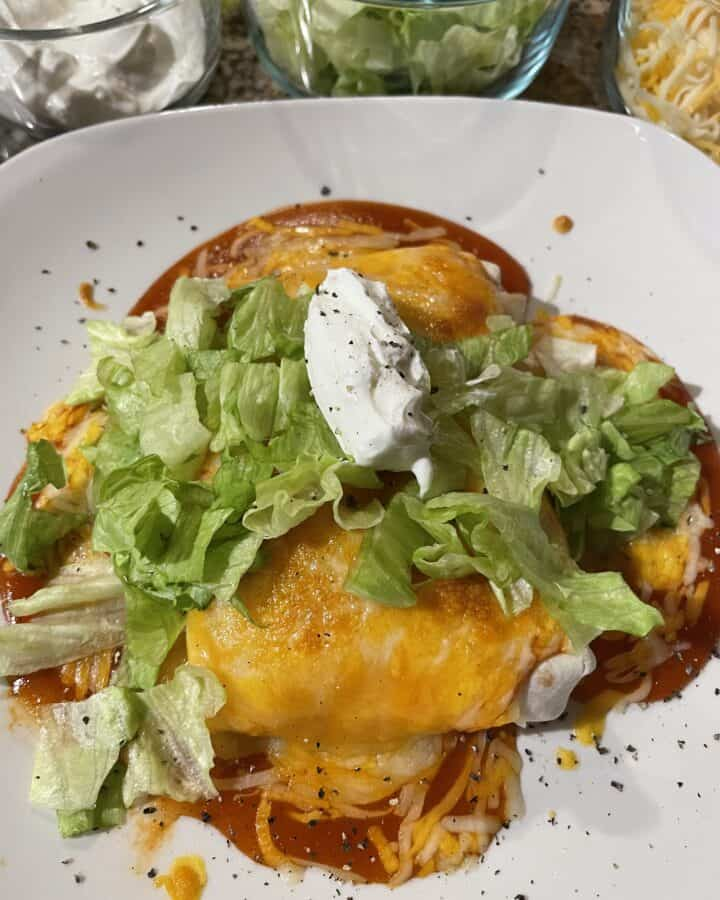 Wet Burrito topped with lettuce and sour cream