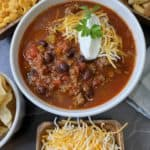 Best Venison Chili Recipe in a white bowl surrounded by different toppings.