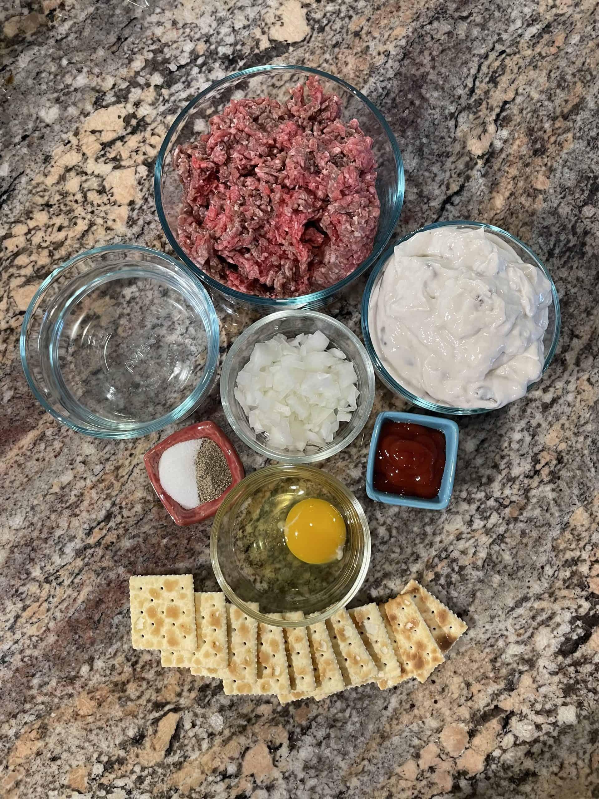 Swedish Meatball Recipe Ingredients - hamburger, diced onion, egg, saltine crackers, ketchup, cream of mushroom soup, salt and pepper.