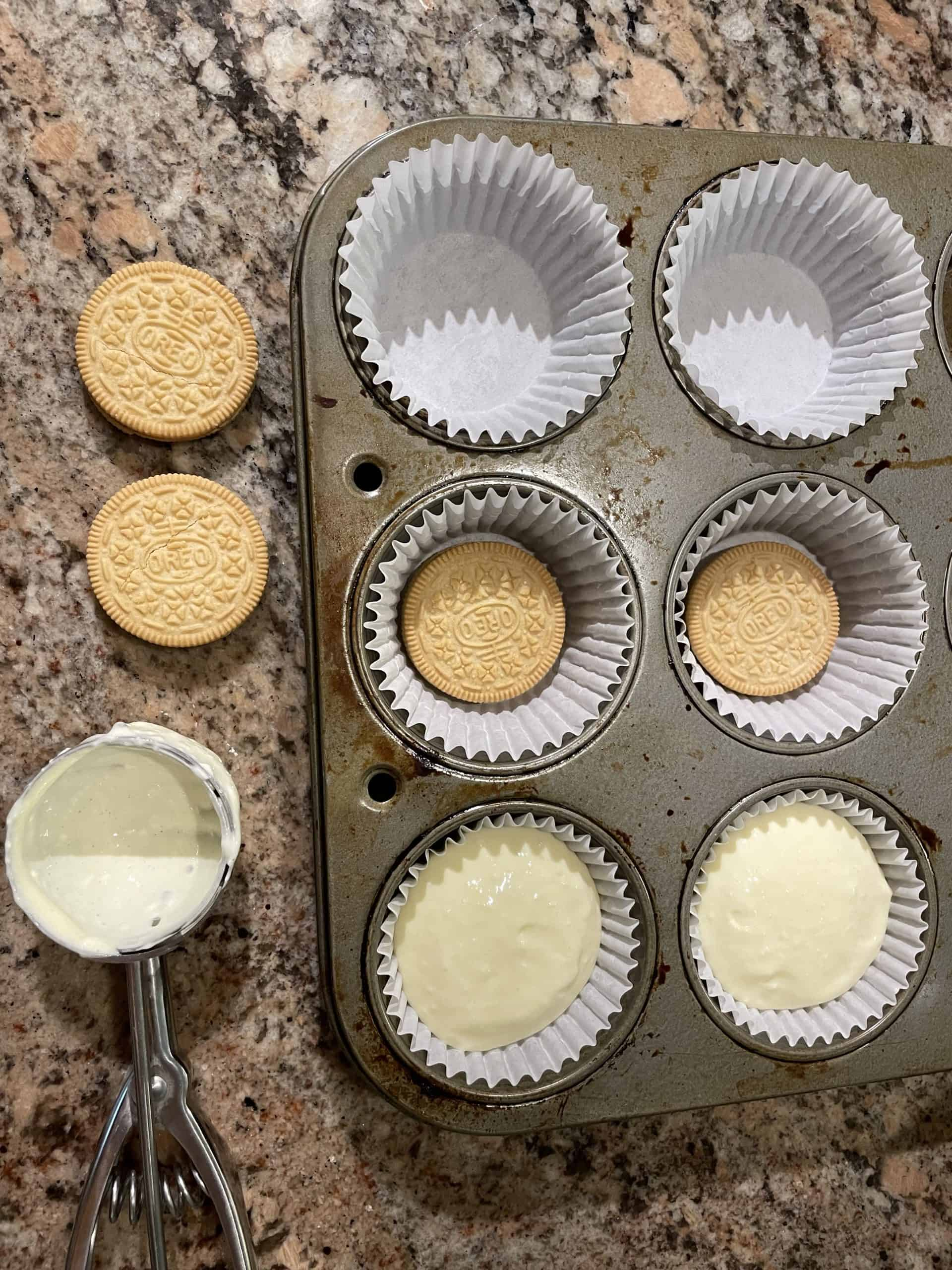 In a cupcake pan place a paper liner, then an Oreo and top with cheesecake batter.