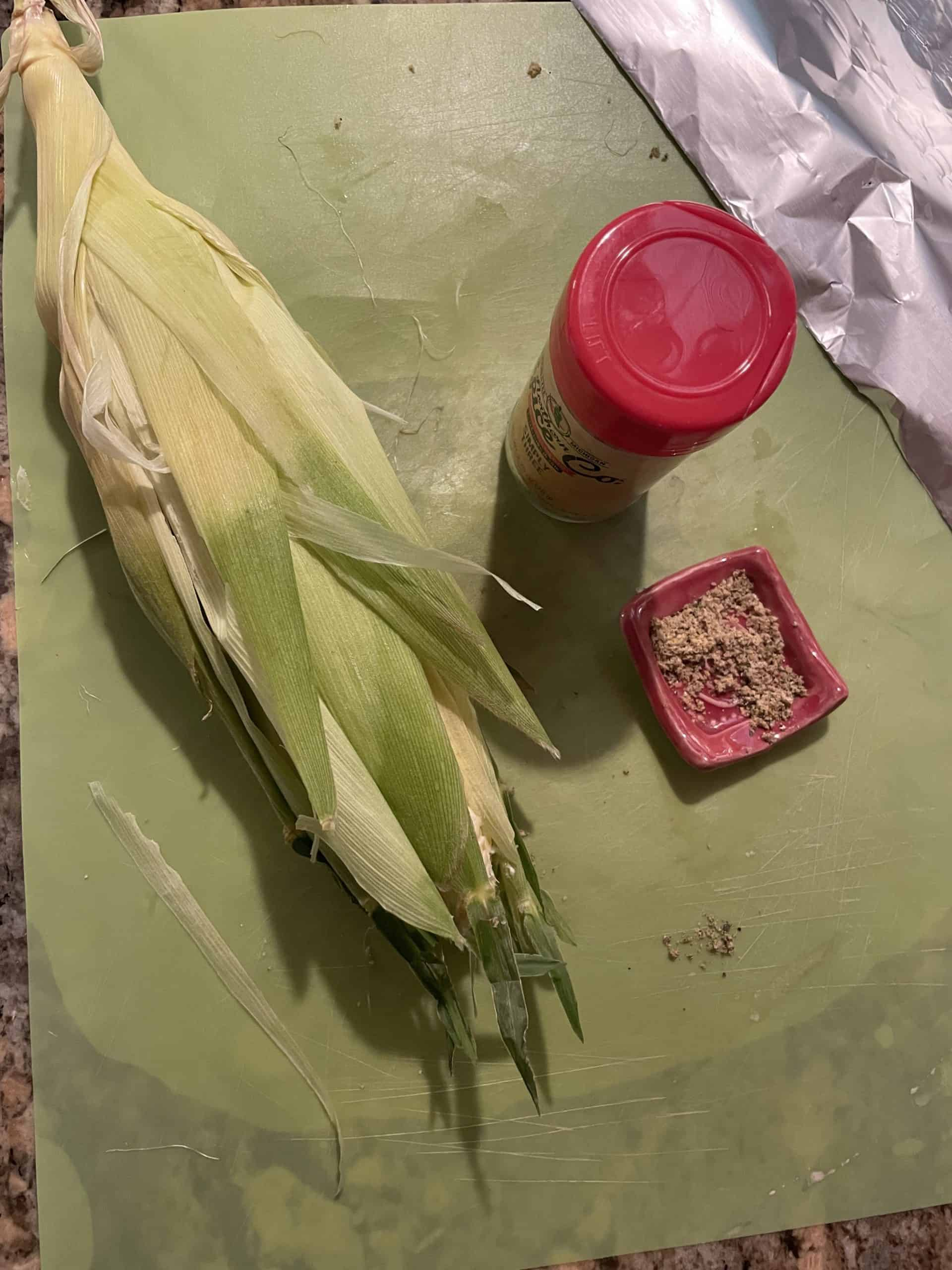 Cover buttered corn with husk.
