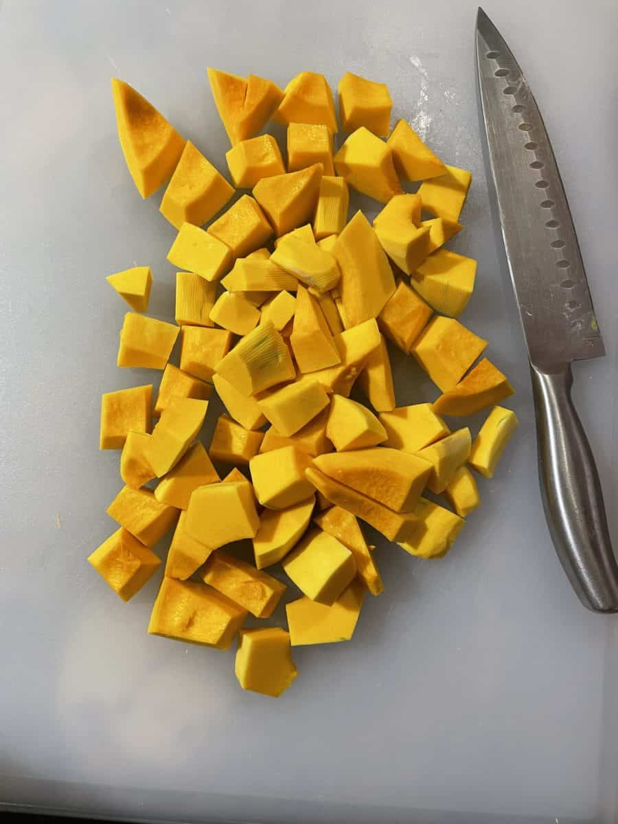 Small dice Butternut squash pieces on a cutting board with a knife.