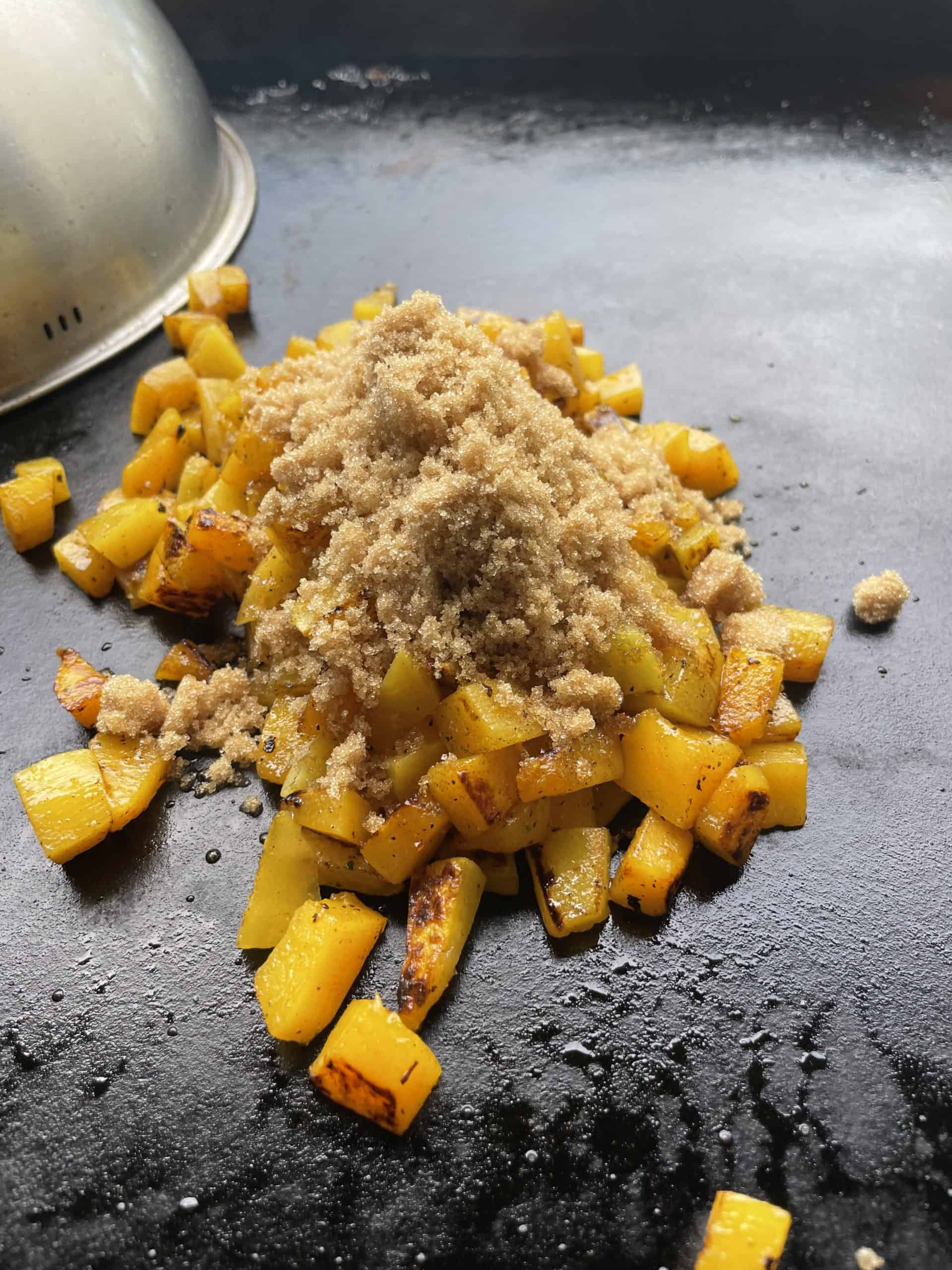 Add brown sugar to the top of griddle cooked butternut squash.
